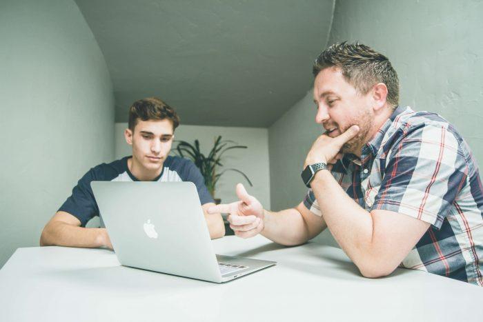 Een man met een laptop legt iets uit aan een jongen, een voorbeeld van kenniswerk