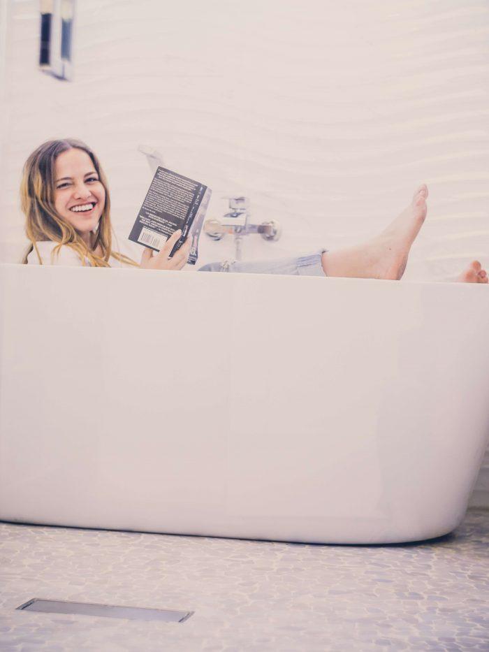 Een vrouw met kleren aan in bad, terwijl ze een zwart boek vasthoudt en naar de camera lacht