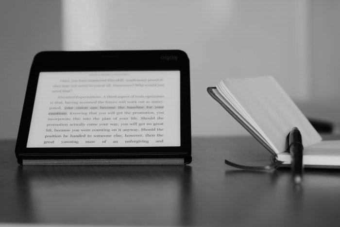 Kobo e-reader, en een fysiek notitieboek met een pen