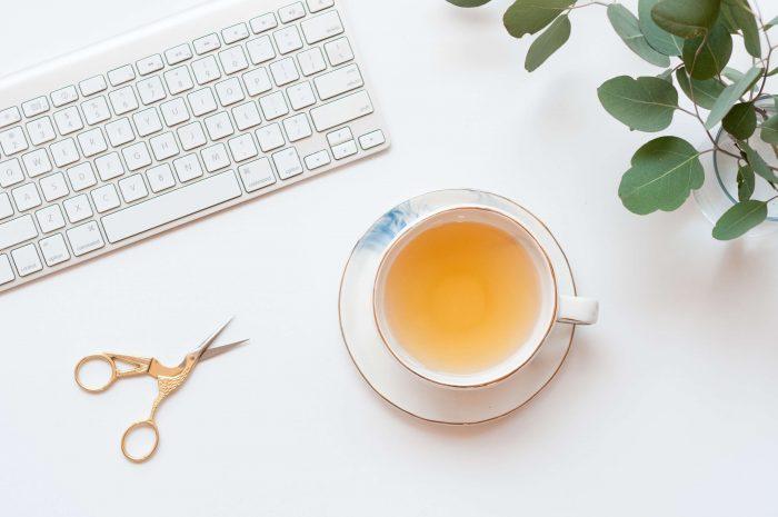 Een kopje thee naast een toetsenbord en schaar
